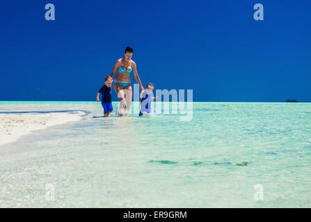 Two small boys running with mother on a tropical bach - Stock Photo