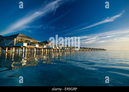 Over water villas in Maldives reflected in blue lagoon before sunset - Stock Photo