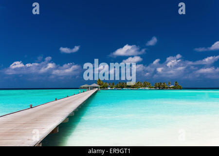 Wooden jetty to a tropical island over amazing lagoon in Maldives - Stock Photo