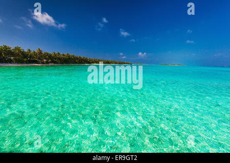 Tropical island with sandy beach, clear sky and pristine water - Stock Photo
