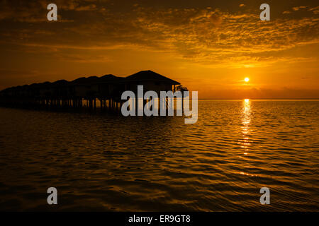 Maldives sunset with water villas silhouette and cloudy sky - Stock Photo