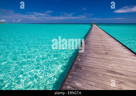 Wooden long jetty over lagoon in Maldives with amazing clean water - Stock Photo