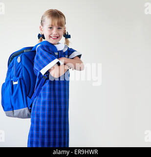 Little girl dressed in her school uniform and backpack ready to go to school - Stock Photo