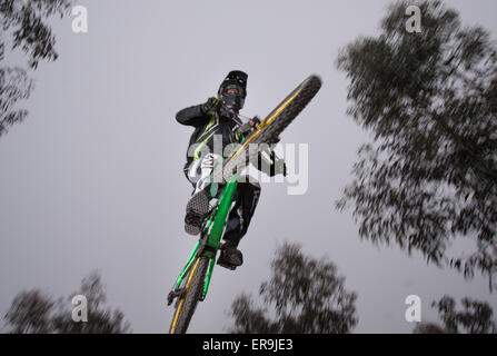 Mountain biker on a downhill course jumping through the air - motion blur - Stock Photo