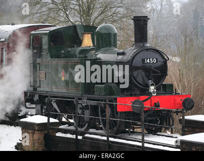 One of Britain's smaller locomotives, No.1450 0-4-2 Tank engine waits just outside of a snowy Highley - Stock Photo