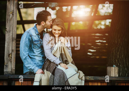 Young couple wrapped in plaid - Stock Photo