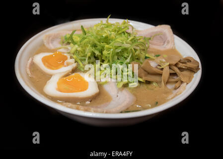 Closeup of a ramen  noodle soup with porc, chives, eggs, bamboo and leek isolated on black background - Stock Photo