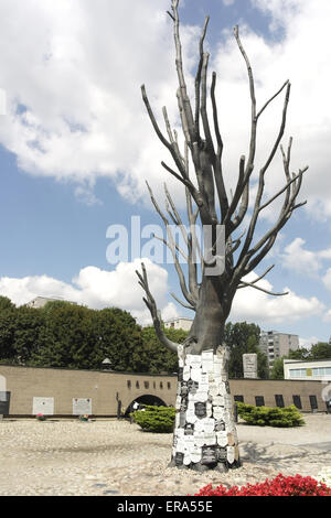 Blue sky white clouds portrait, to museum entrance, memorial tree with obituary plaques Gestapo victims, Pawiak - Stock Photo