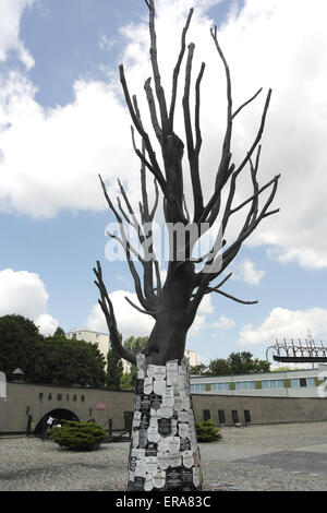 Blue sky white clouds portrait bronze memorial tree with obituary plaques Gestapo victims, Pawiak Prison Museum, - Stock Photo