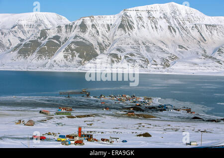 Snow-covered mountains at Isfjorden and the small industrial port of Longyearbyen, photographed from the entrance - Stock Photo