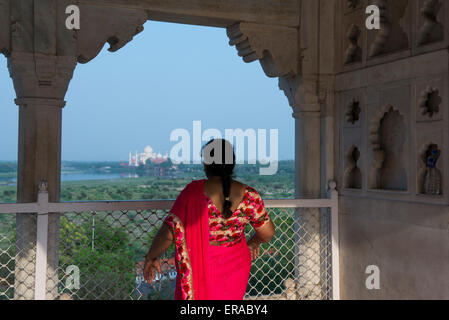 India, Agra. View of the Taj Mahal from the Red Fort of Agra. Woman in traditional sari looking at view of Taj. - Stock Photo