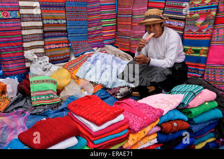 Woman selling clothing and textiles at Sunday market, Quiquijana (near Cuzco), Peru - Stock Photo