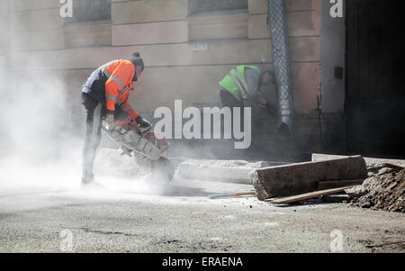 A Road Construction Worker Cutting Stone For The Kerb