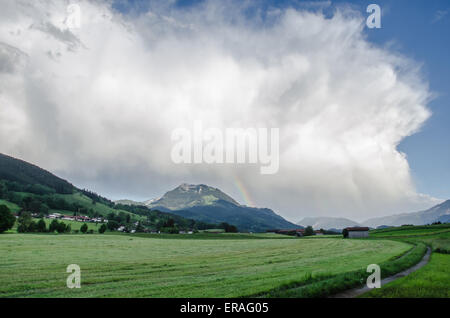 Sunset and a rising storm over agricultural land in the Bavarian Alps - Stock Photo