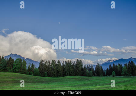 Sunset and a rising storm over agricultural land and a forest in the Bavarian Alps - Stock Photo
