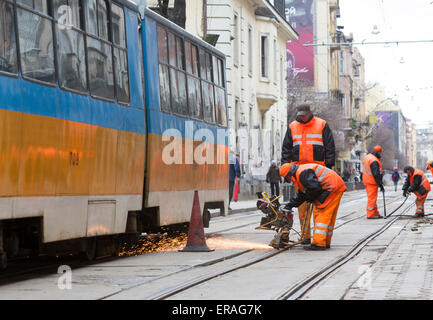 Sofia, Bulgaria - April 7, 2015: Tram road workers are repairing the tram tracks on the tram road. - Stock Photo