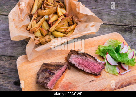 Medium rare grilled top rump steak seasoned with green pepper and thyme, served on a wooden board with rosemary - Stock Photo