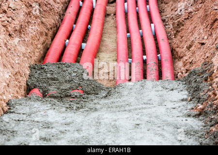 Concreting red corrugated pipes for electrical installation. - Stock Photo