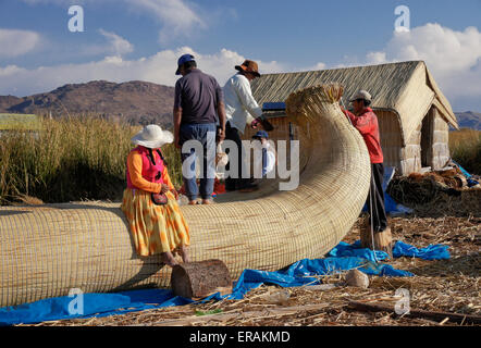 Uros Indians building boat from tortora reeds on floating island in Lake Titicaca, Puno, Peru - Stock Photo