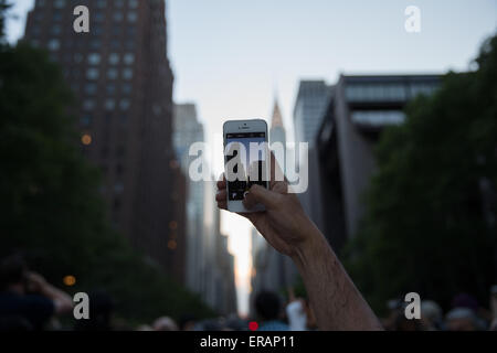 New York, USA. 30th May, 2015. A man waits to take photos of 'Manhattanhenge' in the Manhattan, New York, the United - Stock Photo