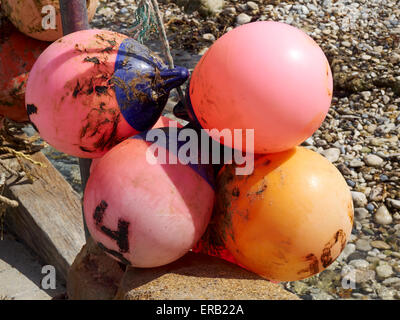 Brightly coloured but heavily used and worn marker buoys used by fishermen to mark the location of crab and lobster - Stock Photo