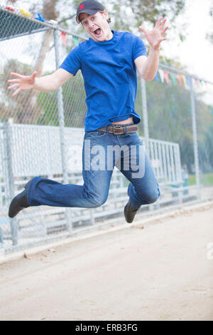 young man jumping on a sports field - Stock Photo