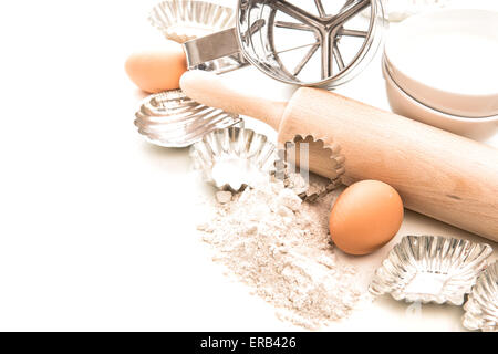 Flour, eggs, rolling pin and cookie cutters on white background. Baking ingredients and tolls for dough preparation - Stock Photo