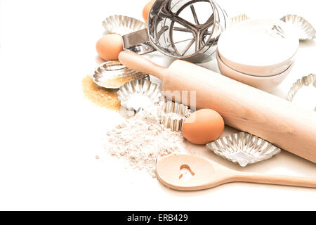 Baking ingredients and tolls for dough. Flour, eggs, rolling pin and cookie cutters over white background - Stock Photo
