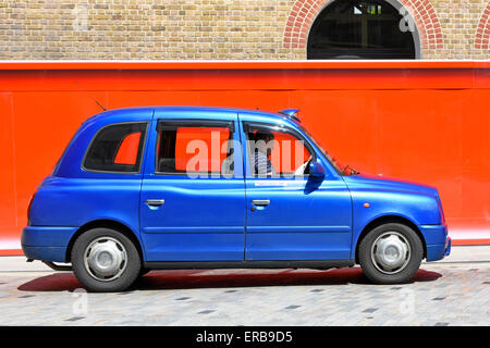 London taxi cab driver reads his paper whilst queuing for customers at Kings Cross station Camden beside orange - Stock Photo