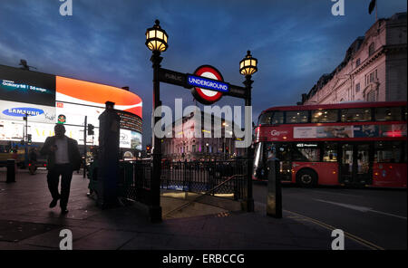 A man walks by a Tube entrance near a double-decker bus in Piccadilly Circus, in London, England, 2015. (Adrien - Stock Photo