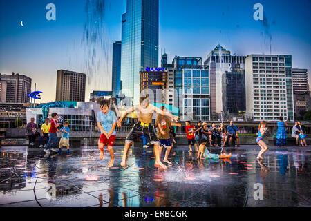 Children splashing in the illuminated fountain at night against illuminated city on Yarra  promenade, Melbourne - Stock Photo