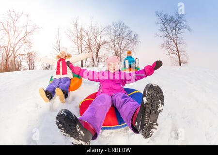 Girl and her friends sliding down hill on tubes - Stock Photo