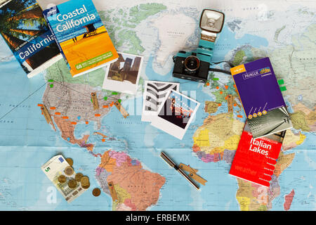 Travel planning. Map of the world, guide books, currency, photographs. - Stock Photo