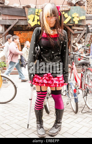 Japan, Osaka, Dotonbori. Woman with glasses, stands in street, posing shyly in Lolita Goth cosplay outfit. Eye-contact. - Stock Photo