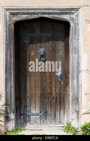 Old brown wooden door with metal studs and ornate hinges - on historic building near Lapworth, England - Stock Photo