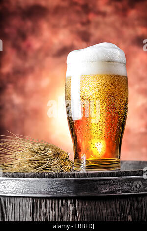 Glass of beer with wheat ears on a wooden barrel - Stock Photo