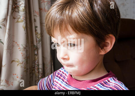 3 - 5 year old Caucasian child, boy. Head & shoulder, side-view, alone, looking sadly out of window (unseen), by - Stock Photo