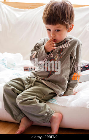 2 - 4 year old Caucasian child, boy. Indoors, sitting on edge of futon, bed, looking down, biting nails and looking - Stock Photo
