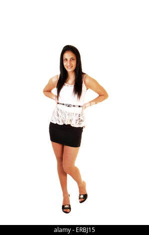 A slim teenager girl standing for white background, wearing a short black skirt and white blouse and high heels. - Stock Photo