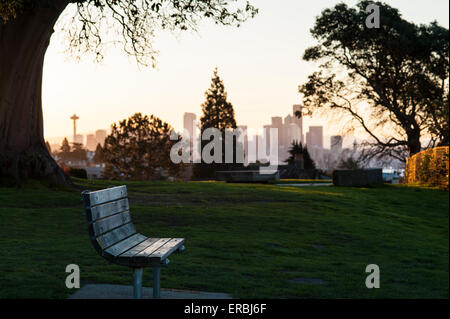 Seattle Skyline from Magnolia Bluff sunrise with with park bench - Stock Photo