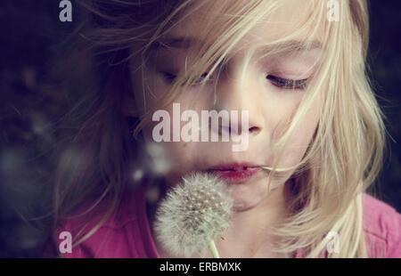 Portrait of caucasian blond girl blowing flower dandelion seeds - Stock Photo