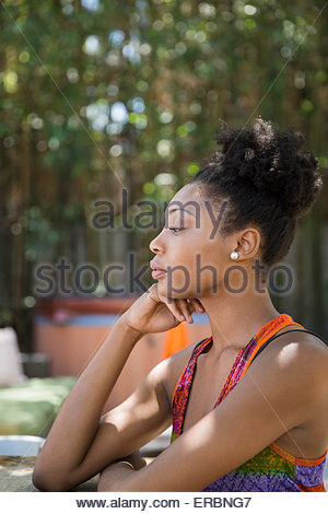 Profile of pensive woman sitting on patio - Stock Photo