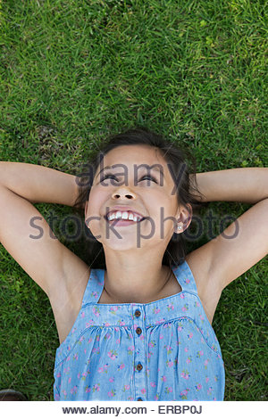 Smiling girl laying in grass hands behind head - Stock Photo
