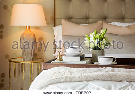 Tea tray and flowers on elegant bed - Stock Photo