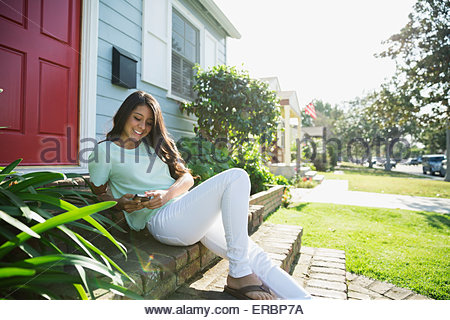 Teenage girl texting with cell phone font stoop - Stock Photo