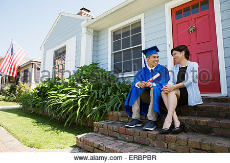 Smiling graduate and mother on front stoop - Stock Photo