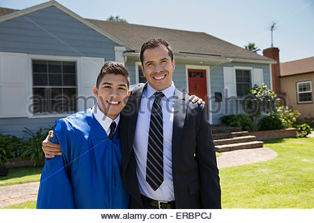 Portrait father and graduate son in front yard - Stock Photo
