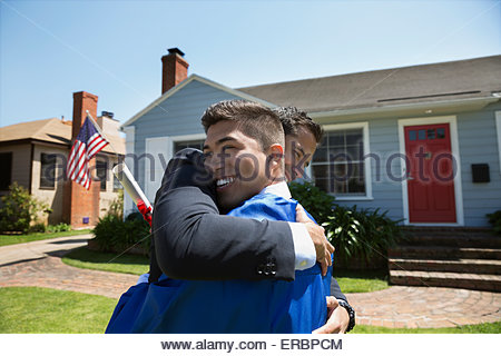 Father and graduate son hugging in front yard - Stock Photo