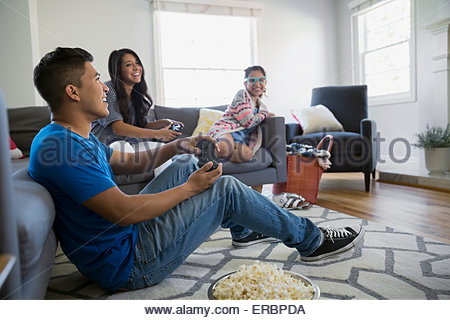 Brother And Sisters Playing Video Game Living Room