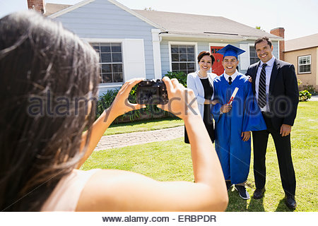 Sister photographing graduate brother and parents front yard - Stock Photo
